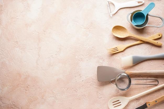 Verschiedene küchenutensilien auf beige mit platz für text. flach liegen.