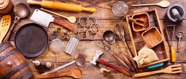 Verschiedene küchenutensilien auf holztisch-draufsichtfahne