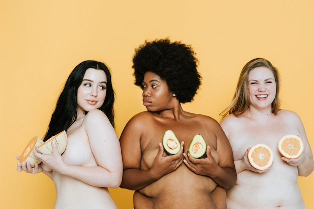 Verschiedene kurvige nackte frauen, die früchte über ihren brüsten halten