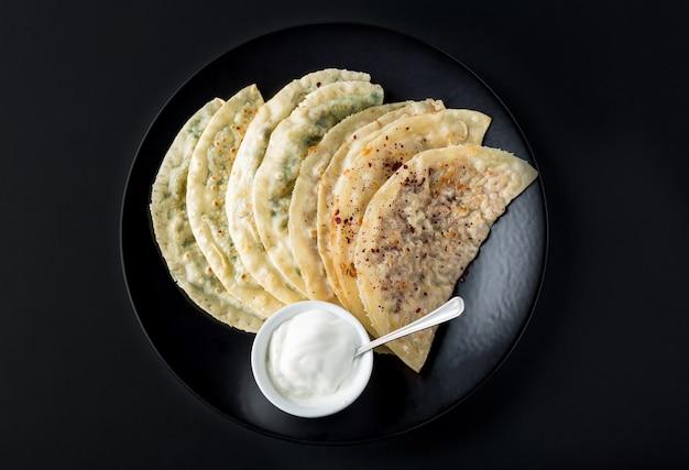 Verschiedene kutabs nationaler küche aserbaidschans mit soße auf schwarzblech.