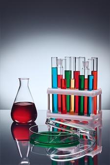 Verschiedene laborglaswaren mit farbflüssigkeiten auf tisch mit reflexion