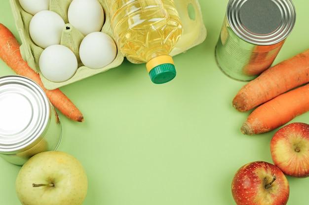 Verschiedene lebensmittelprodukte liegen auf grünem hintergrund. langfristige lebensmittelversorgung. draufsicht, freier speicherplatz.