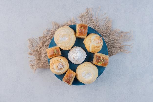 Verschiedene leckere desserts auf holzbrett.