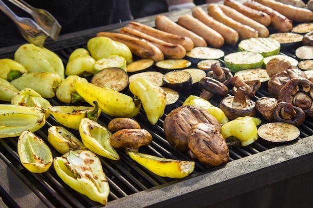 Verschiedene leckere gegrillte fleischsorten mit gemüse über dem grill auf der holzkohle. würstchen, steak, pfeffer, champignons, zucchini.