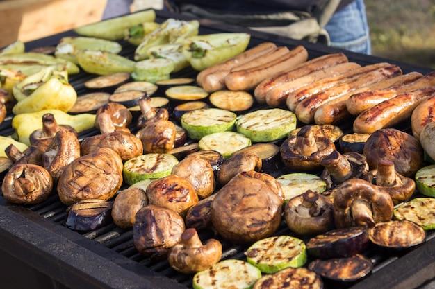 Verschiedene leckere gegrillte fleischsorten mit gemüse über dem grill auf der holzkohle.