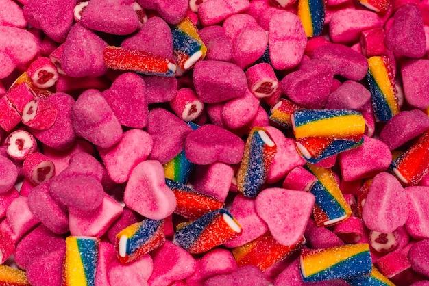 Verschiedene leckere gummibonbons. ansicht von oben. rosa geleebonbons hintergrund.