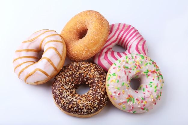 Verschiedene leckere hausgemachte donuts in der glasur, bunte streusel und nüsse.