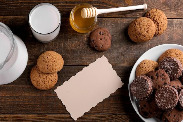 Verschiedene leckere kekse mit honig und milch auf einem braunen holztisch. sicht von oben
