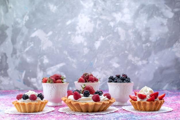Verschiedene leckere kuchen mit sahne und frischen beeren auf hellem schreibtisch, beerenfruchtkuchen-keks