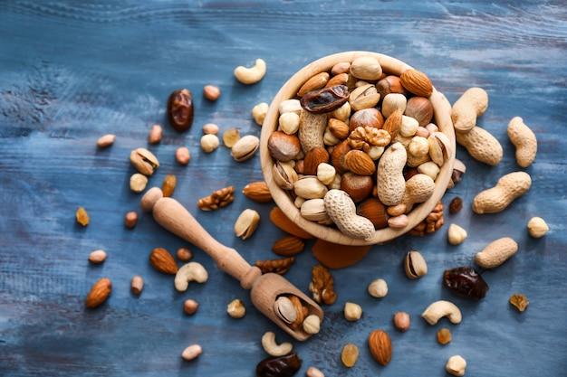 Verschiedene leckere nüsse mit schüssel und schaufel auf farbfläche