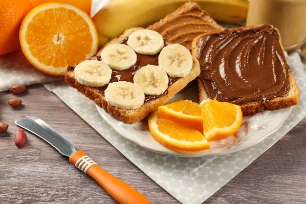 Verschiedene leckere sandwiches mit erdnussbutter und früchten auf teller