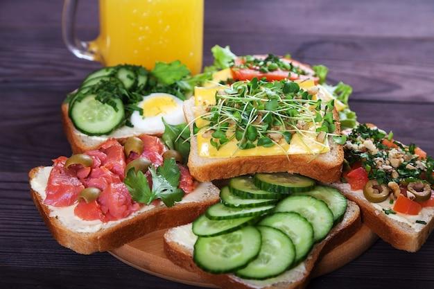 Verschiedene leckere sandwiches mit lachs, sprossen, tomaten, gurken, kräutern, nüssen, oliven und frischem orangensaft