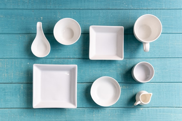 Verschiedene leere weiße platten und schüsseln auf hölzernem hintergrund, draufsicht