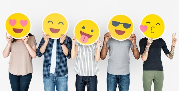 Verschiedene leute, die glückliche emoticons halten