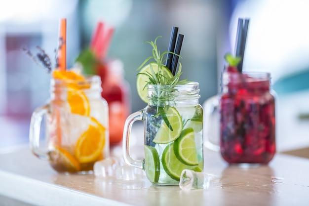 Verschiedene limonaden in einmachgläsern mit orangen-limonen-zitronen-otange-erdbeeren und frischen obstfrüchten.