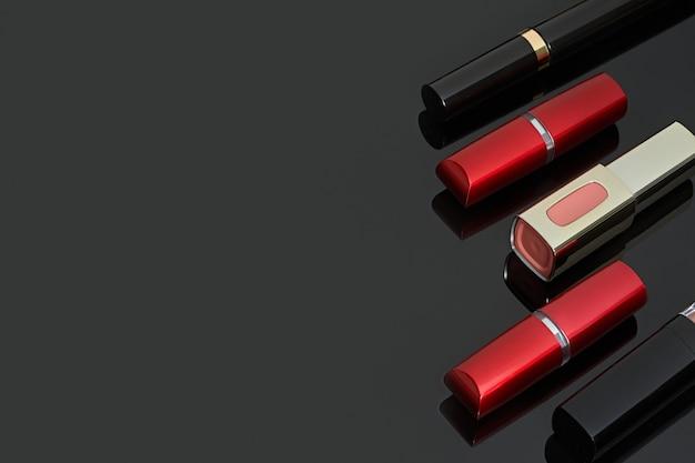 Verschiedene lippenstifte auf einem dunklen spiegelhintergrund.