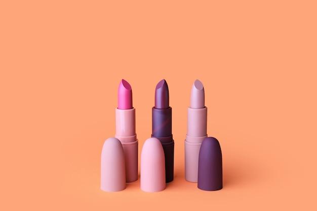Verschiedene lippenstifte auf farbigem hintergrund