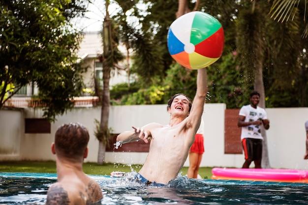 Verschiedene männer, die aufblasbaren ball des strandes im swimmingpool spielen