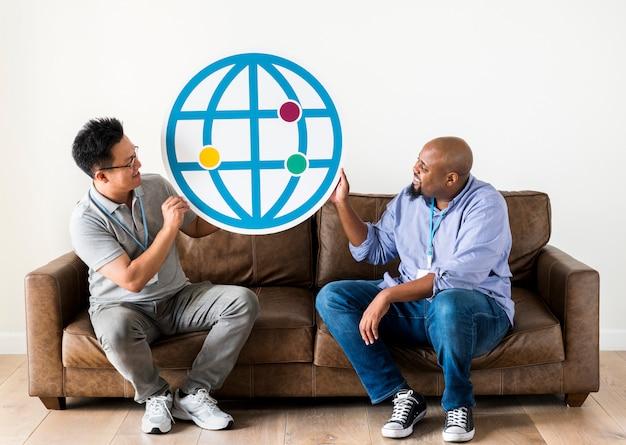 Verschiedene männer, die die browserikone sitzt auf couch halten