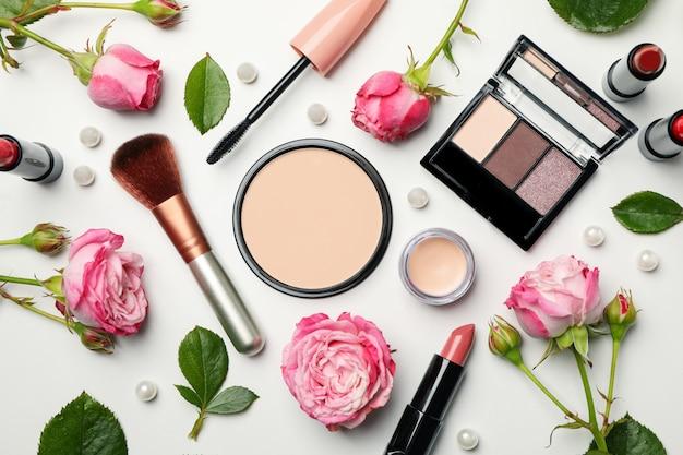 Verschiedene make-up-kosmetik und blumen auf weißem hintergrund. weibliches zubehör