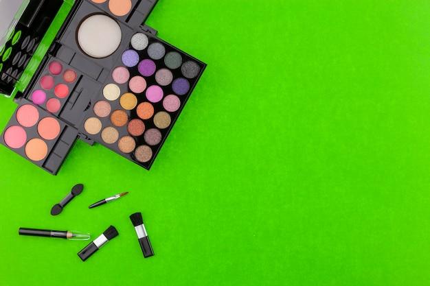 Verschiedene make-up pinsel, lidschatten und kosmetik auf bunten grünbuch hintergrund