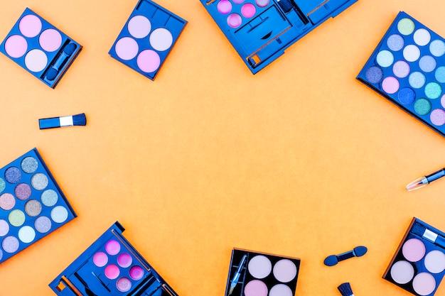 Verschiedene make-up pinsel, lidschatten und kosmetik auf bunten orange papierhintergrund