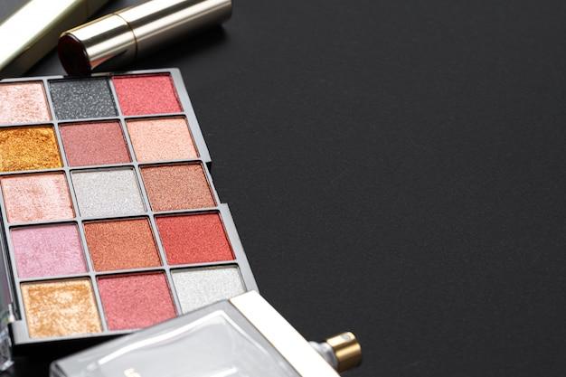 Verschiedene make-up-produkte auf schwarzem textur-tisch. nahansicht