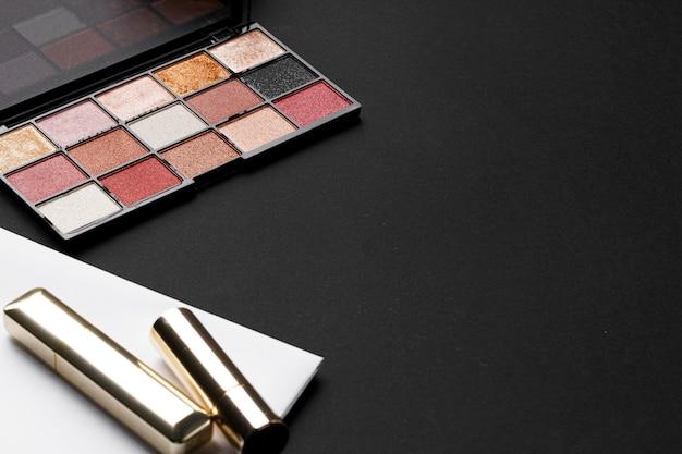 Verschiedene make-up-produkte auf schwarzem texturhintergrund. nahansicht