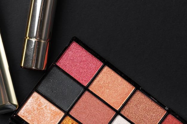 Verschiedene make-up-produkte auf schwarzer oberfläche