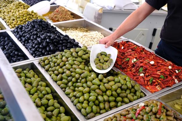 Verschiedene marinierte oliven zum verkauf in einem marktfenster.