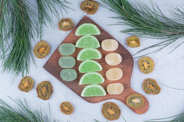 Verschiedene marmeladen auf holzbrett mit getrockneten kiwischeiben.