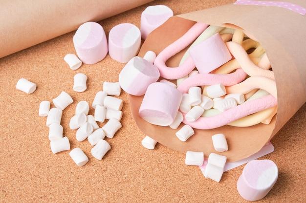 Verschiedene marshmallows in geschenkpapier, korkhintergrund, umweltfreundliches lebensstilkonzept