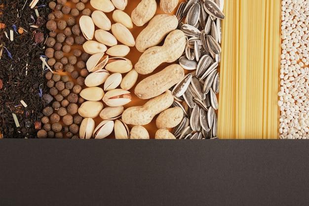 Verschiedene massenprodukte aus lebensmitteln texturieren draufsicht auf einen kopierraum, samen, nüsse, tee, gewürze, getreide und nudeln unter einem schwarzen blatt papier, mock-up