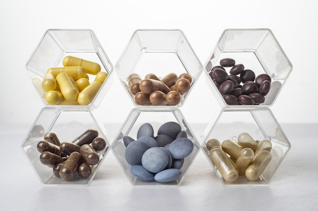 Verschiedene medizinische kapseln und tabletten in hexagonalen transparenten gläsern ähnlich der zelle