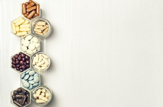 Verschiedene medizinische kapseln und tabletten in sechseckigen gläsern in form von waben