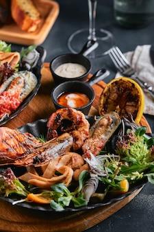 Verschiedene meeresfrüchte auf tellern schöne komposition auf einem servierten meeresfrüchtetisch, tintenfisch, garnelen, lachssteak und tintenfisch