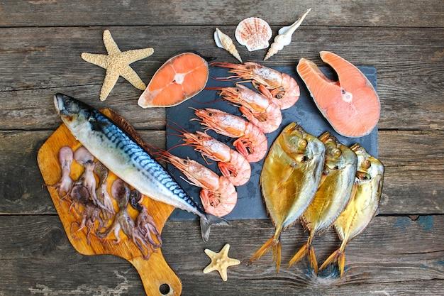 Verschiedene meeresfrüchte: fisch, garnelen, tintenfisch. ansicht von oben. flach liegen.