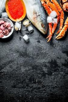Verschiedene meeresfrüchte mit eiswürfeln. auf schwarzem rustikalem hintergrund