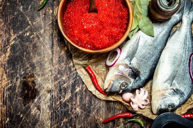 Verschiedene meeresfrüchte mit garnelen und rotem kaviar. auf einem hölzernen hintergrund.