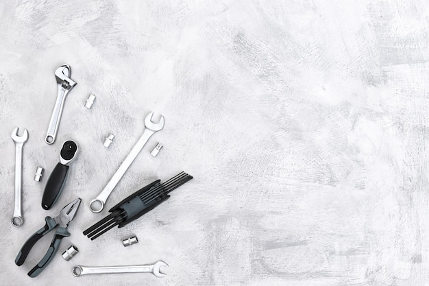 Verschiedene metallwerkzeuge zangen schraubenschlüssel schraubendreher bits draufsicht auf einen grauen betonboden