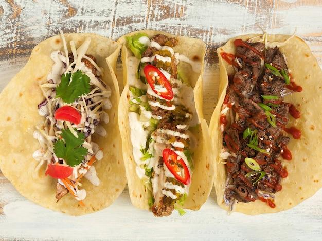 Verschiedene mexikanische tacos: huhn, rind und schweinefleisch mit gemüse