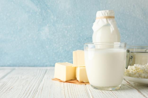 Verschiedene milchprodukte auf weißem holztisch gegen blauen raum, kopierraum