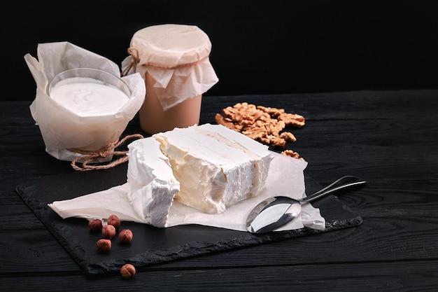 Verschiedene milchprodukte milch, joghurt, hüttenkäse, sauerrahm. rustikales stillleben. milchprodukte von bauernkuh.