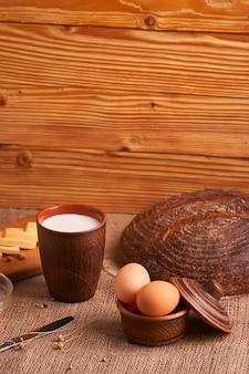 Verschiedene milchprodukte milch, käse, eier. rustikales stillleben auf tisch