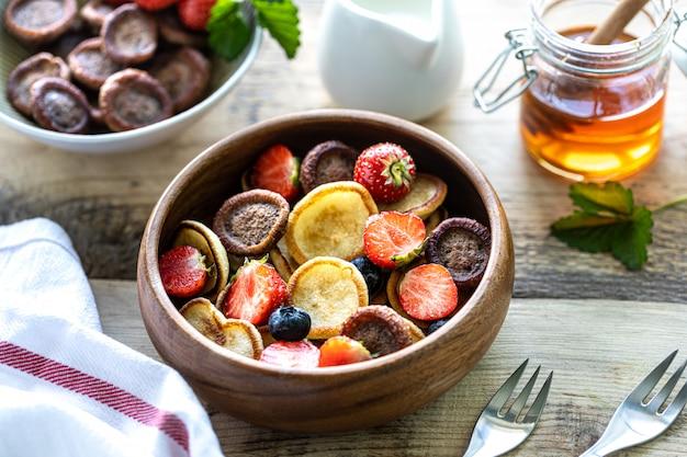 Verschiedene mini-pfannkuchen in einer holzschale mit honig, milch und blaubeeren auf einem holztisch. trendiges essen