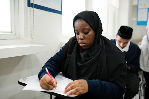 Verschiedene moslemische kinder, die im klassenzimmer studieren