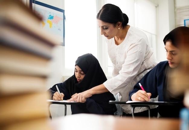 Verschiedene moslemische mädchen, die im klassenzimmer studieren