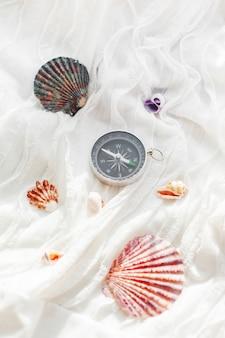 Verschiedene muscheln und kompass. seekorallen auf stoff mit rüschen.