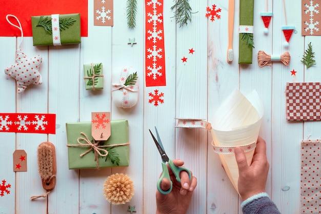 Verschiedene natürliche dekorationen für weihnachts- oder neujahrswinterferien, bastelpapierpakete und umweltfreundliche geschenke ohne abfall. flach lag auf holzbrettern, hände dekorierten sperrholzkegel, schnur und evergreens.