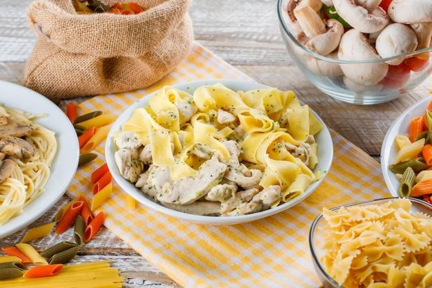 Verschiedene nudelgerichte in tellern mit rohen nudeln und pilzen